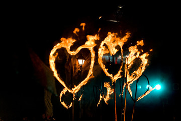 Evening street performance with fiery torches in the form of hea