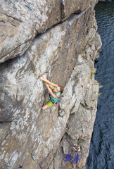 Two young female extreme climbers climb the rock