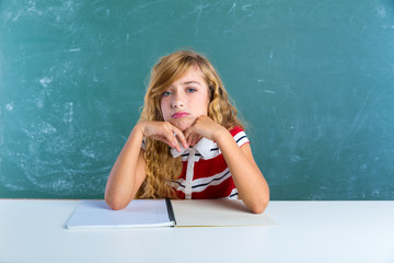 Boring sad expression student schoolgirl on desk