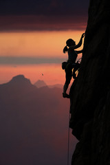 Elegant female alpine climber ascents rock against sunset