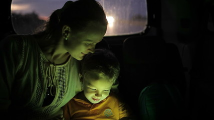 Little boy using tablet pc during car travel  at night