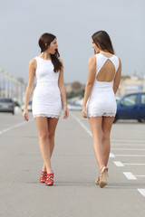 Two women with the same dress looking each other with hate