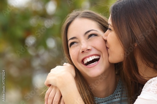 Woman laughing with perfect teeth while a friend is kissing her - 77070224