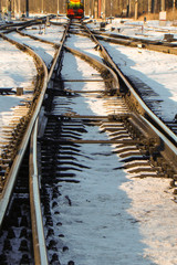rails in the sun in the snow with turnouts in the foreground