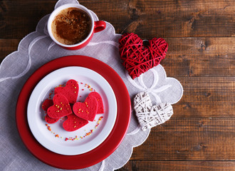 Cookies in form of heart in plate with cup of coffee
