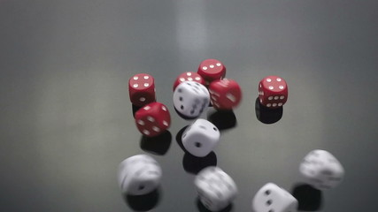 red and white dice cast on black slow motion