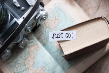 """Just go"" book, map, camera, travel concept."