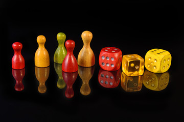 Yellow, red and green figures and playing dice on black