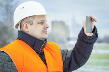 Worker with tablet PC on the field in winter