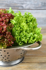 Fresh lettuce in a colander on wooden background