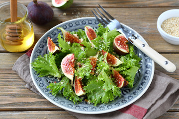 Light salad with figs, lettuce and honey in a plate on napkin