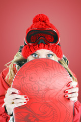 Funny female snowboarder posing with  her snowboard.