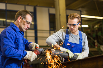 Two workers working with angle grinder
