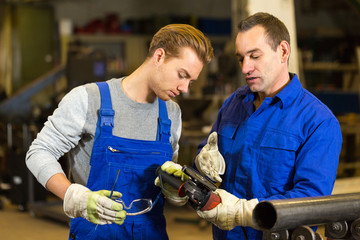 instructor teaches trainee how to use an angle grinder