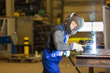 Steel construction worker welds metal parts