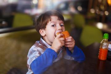 Little boy eat burger behind glass