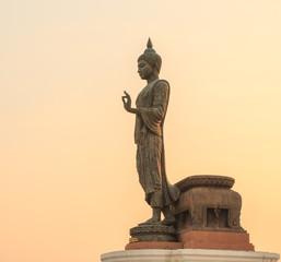 Buddha image against the sunset with orange sky