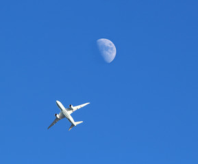 Jet plane and the Moon against a blue sky