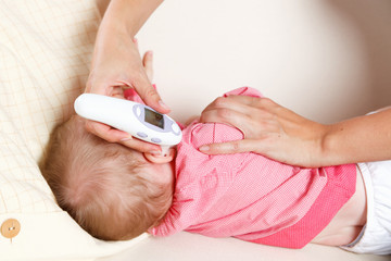 Baby with a digital thermometer