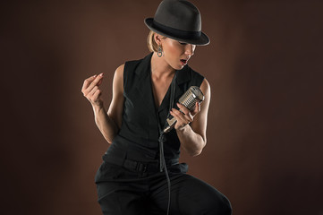 stylish woman in a hat with a retro microphone