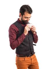 Man wearing waistcoat drinking coffee