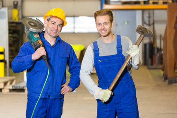 Two steel construction workers posing with angle grinder and ham