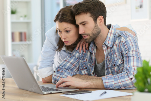 Couple at home websurfing on internet - 77080263