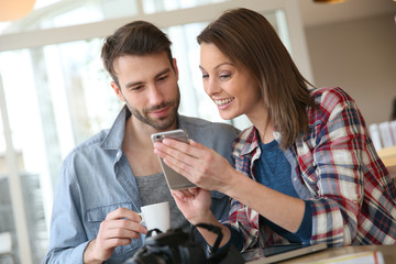 Couple in coffee shop looking at pictures on smartphone