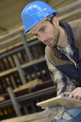 Man in manufacture using digital tablet