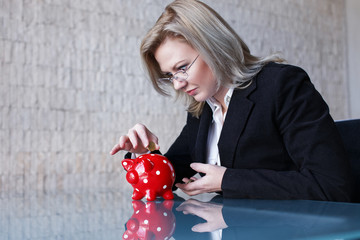 Businesswoman in glasses put coins into red dotted piggy bank