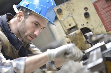 Industrial worker working on machine in factory