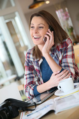 Brunette girl talking on mobile phone in coffee shop
