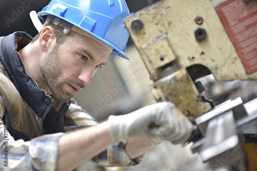 Industrial worker working on machine in factory - 77080860