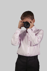 half-length portrait of a boy with a camera in the face on a gra