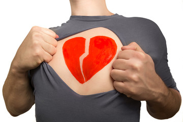Man tearing apart grey t-shirt. Broken red heart painted on his