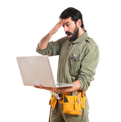 mechanic with laptop over white background