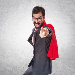 Businessman dressed like superhero pointing to the front