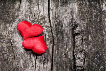 Two satin red hearts on the wooden background