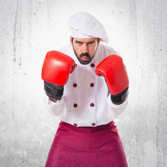 Chef with boxing gloves over white background