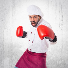 Chef fighting with boxing gloves over white background