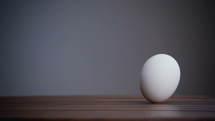 An egg is rolling across the table. Slow motion