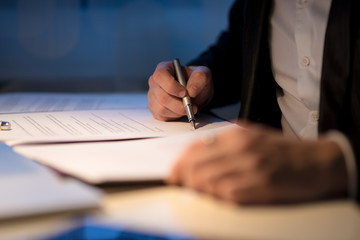 Businessman working late signing a document or contract
