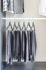row of black pants hangs in wardrobe
