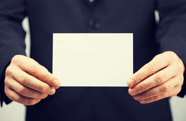 man in suit holding blank card