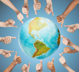 human hands showing thumbs up in circle over earth