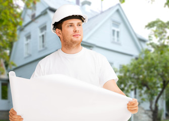 male builder or architect in helmet with blueprint