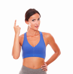 Sporty young looking woman pointing up