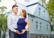 happy young family expecting child over house