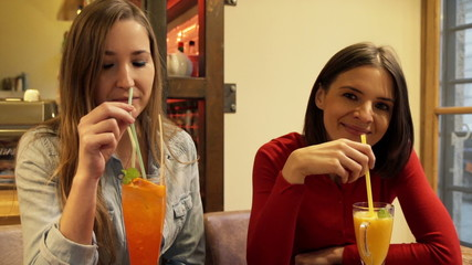 Two happy attractive girlfriends drinking cocktail in cafe