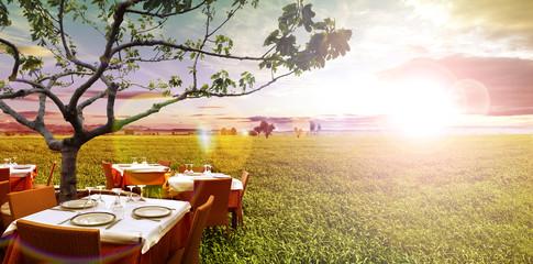 Restaurante al aire libre idílico y campos verdes.Puesta de sol